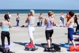 Ontspannen en dynamische yoga op het strand tijdens een yoga vakantie op Terschelling