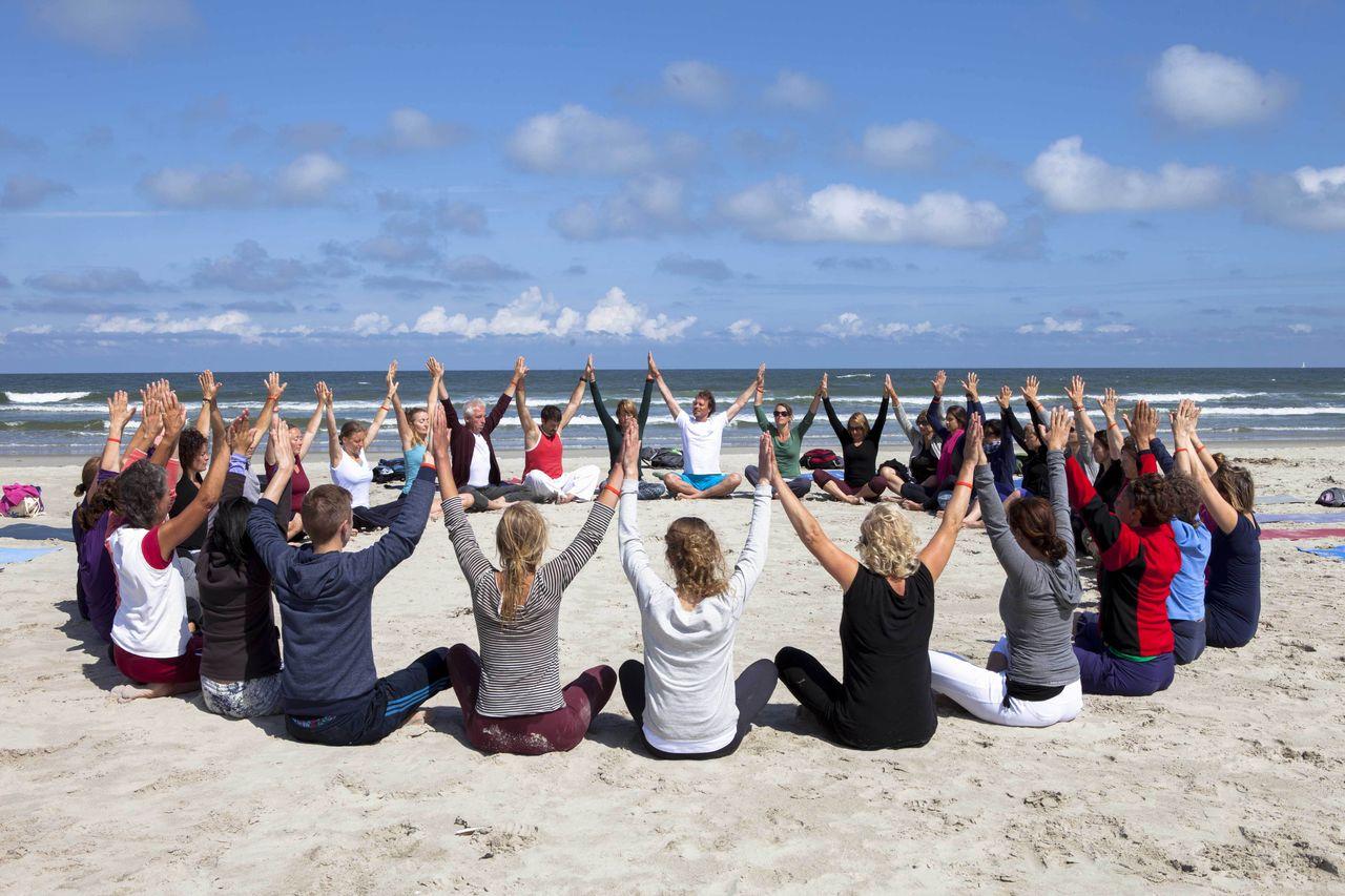 Zon, zee en yoga in een cirkel op het strand tijdens een yoga vakantie